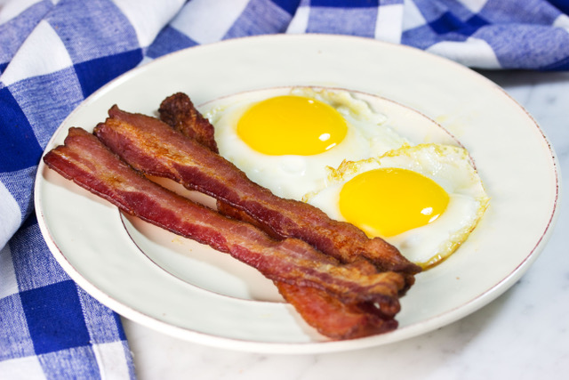bacon cooked in the oven on a plate with sunny side up eggs