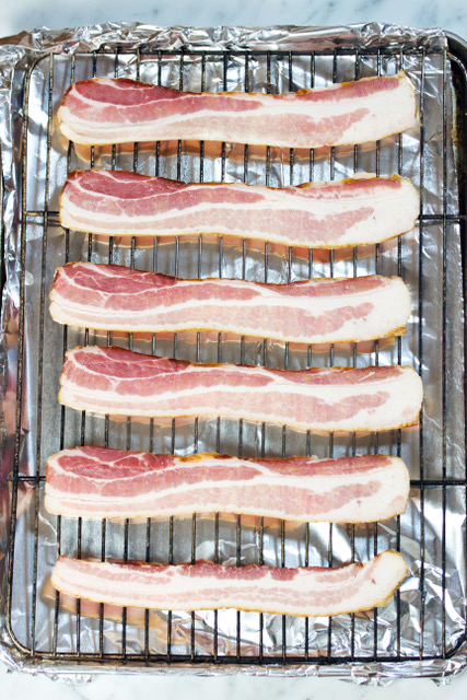 bacon on a raised rack in a baking pan ready to cook in the oven